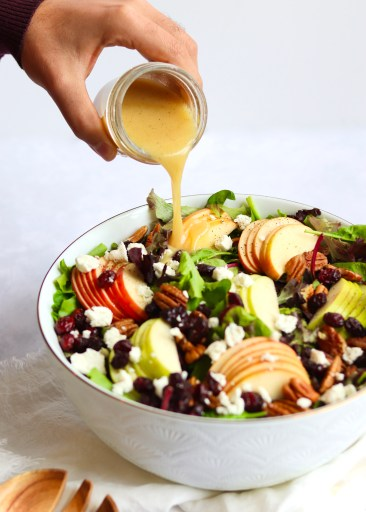 Apple dressing being poured onto a fall salad