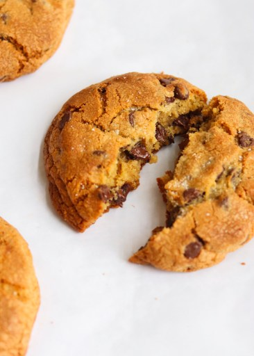 Warm chocolate chip cookie split in half to show the melted chocolate
