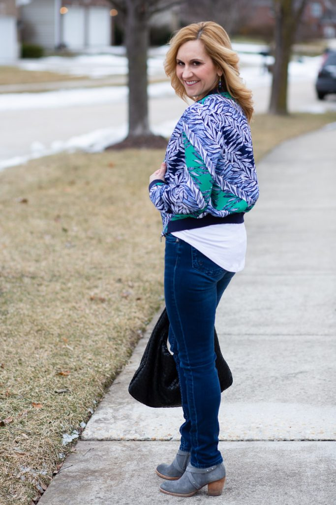 Causal chic look featuring a blue printed bomber jacket, white tee, and dark jeans.