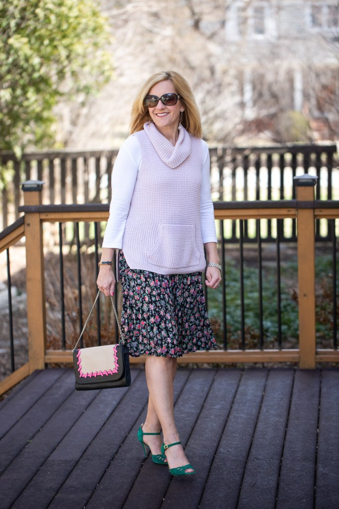 Styling a cozy pink sweater vest with a floral pleated skirt and green heels.
