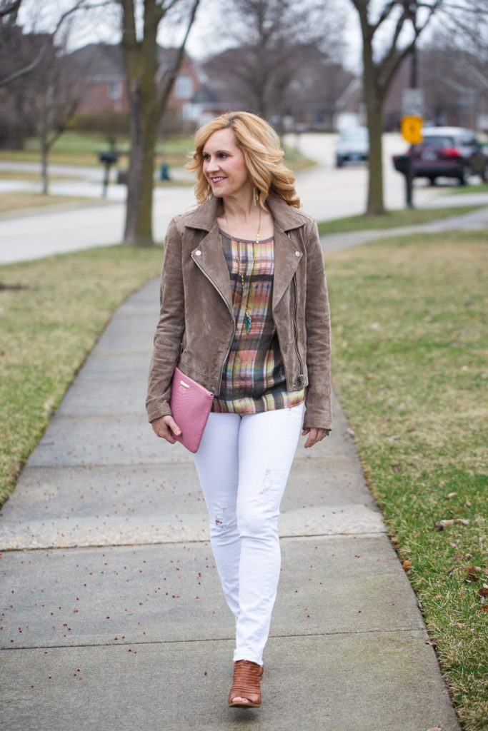 Adding a pink clutch to a spring neutrals look which features a being moto jacket and white jeans.