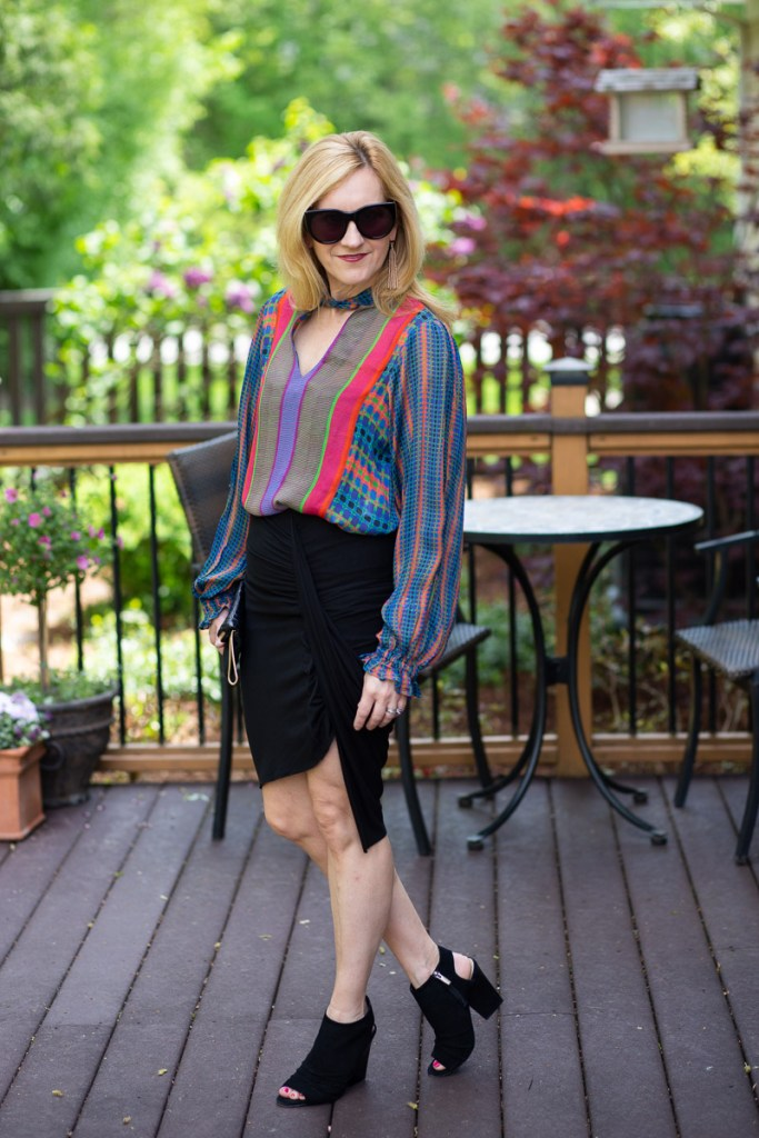 Adding edge to a colorful peasant blouse with an asymmetrical pencil skirt and block sandals.