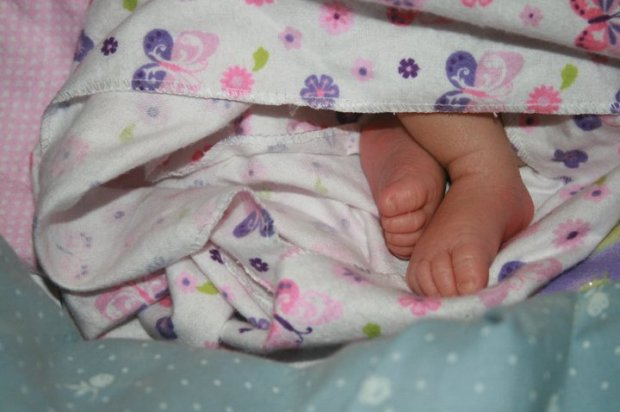 A baby girl's feet poking out of a baby blanket.