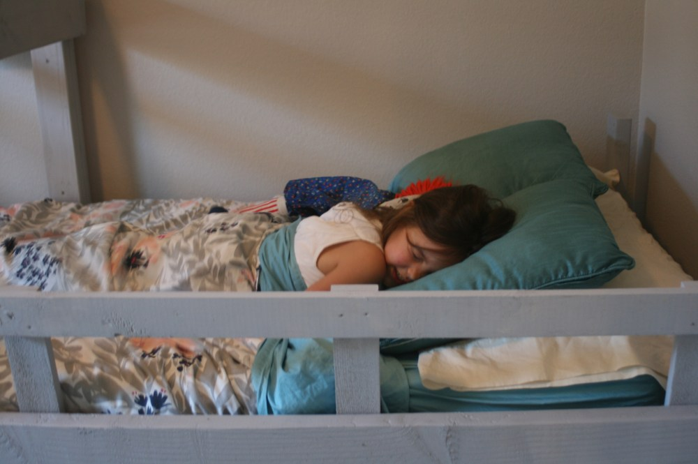 Photo close up of child sleeping in Triple Bunk Bed