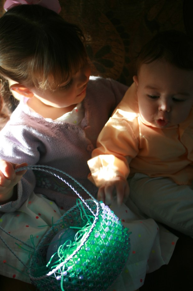 Toddler girl with baby brother on Easter