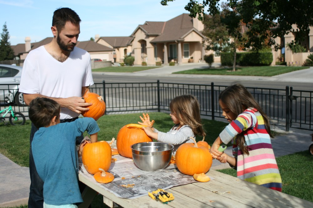 Kids with their dad carving pumpkins