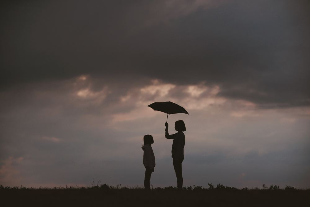 Person holding umbrella for a child with storm clouds in the background to illustrate the role of relationship in gratitude.