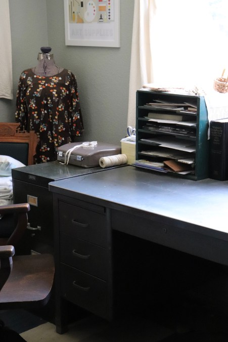 Photograph of home office with dress form and vintage desk organizer