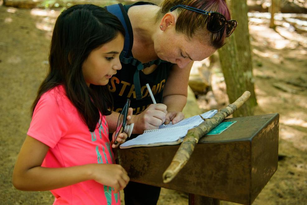 Epic Hikes With Kids - BARRON CANYON TRAIL, signing guest book #discoverON #exploremore #barroncanyontrail #algonquinpark #getoutside #liveoutdoors #ontarioparks #welivetoexplore #familytravelblogger #hikingwithkids #kidswhohike #hikingmom