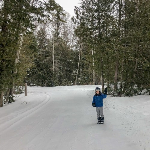 little boy standing on a snowy road winter camping at MacGregor Point Provincial Park