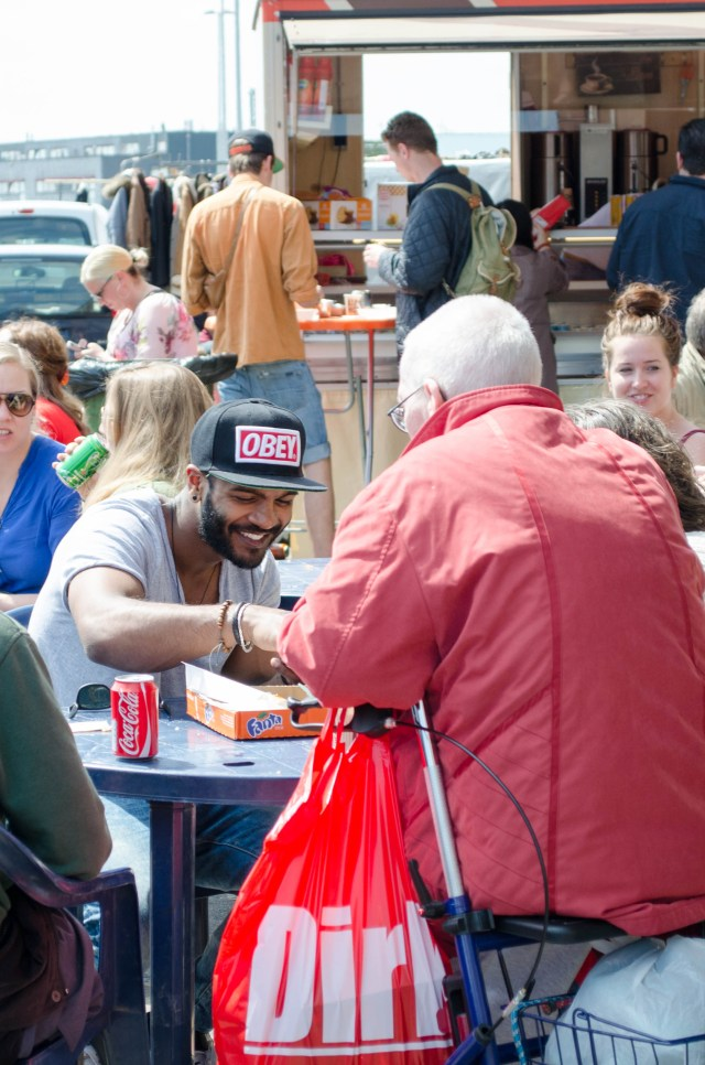 people enjoy the sun and food trucks outside the giant flea market, IJhallen in Amsterdam-Noord