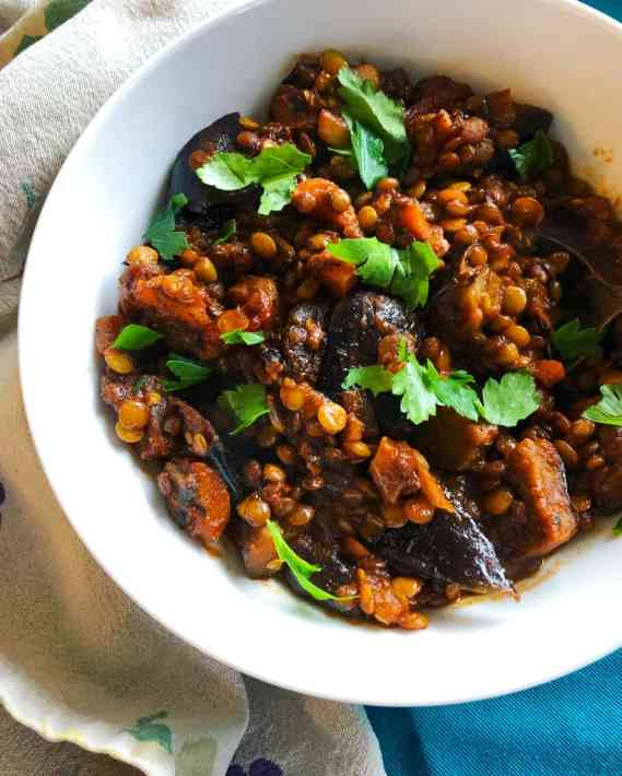 a white bowl filled with vibrant red and orange eggplant and lentil stew, with parsley leaves garnished on top