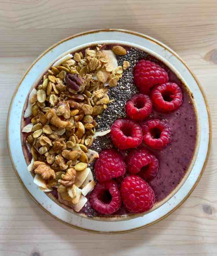white bowl on a light wooden table with a purple smoothie in a white bowl topped with vertical rows of granola, chia seeds, and raspberries