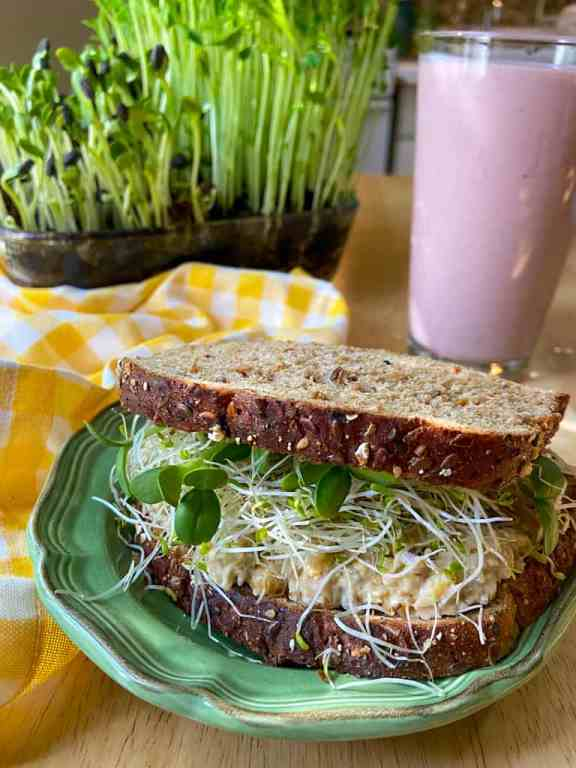 a side view of a sandwich with soft grain bread, chickpea tuna mash, and sprouts inside, with a pink strawberry smoothie in the background, yellow checked napkin and tray of sprouts growing