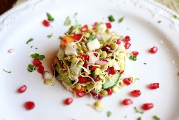 a white, minimalist plate with a salad packed into a ramekin shape and carefully turned onto the plate, garnished with bright pomegranate seeds, herbs, and lentil sprouts