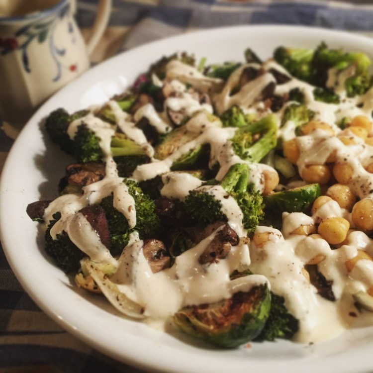 close up image of roasted broccoli, brussels sprouts, and tahini in a white bowl, with creamy tahini dressing poured over it