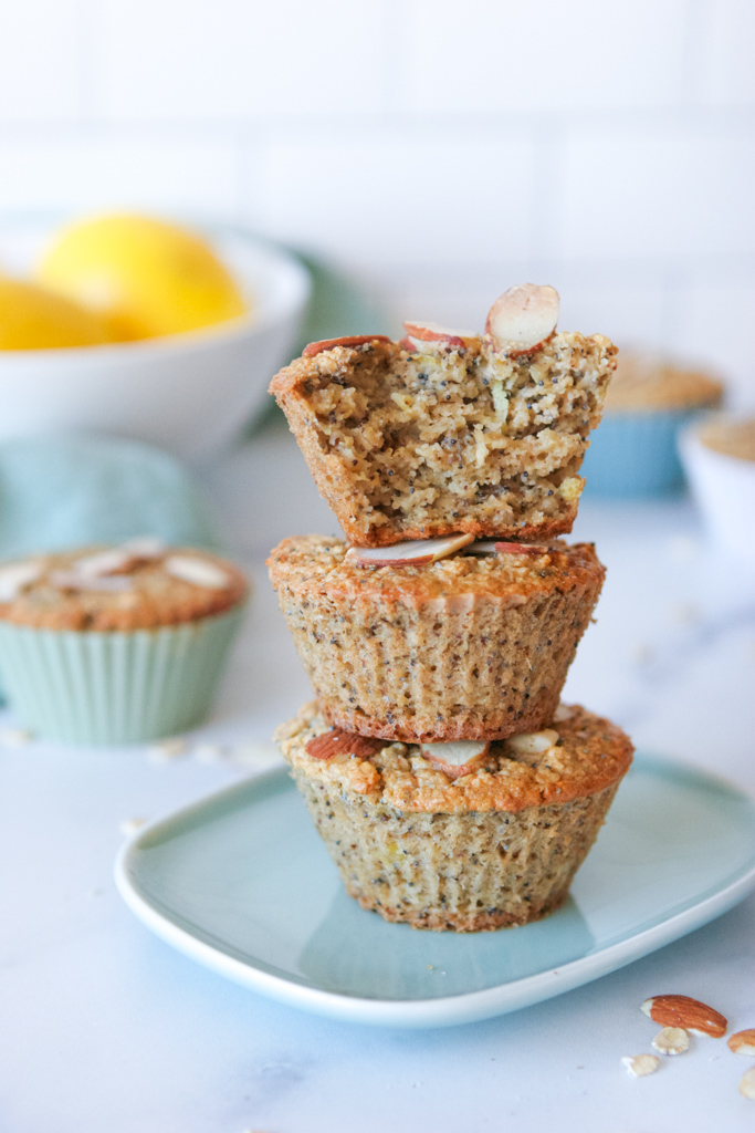 stack of lemon poppyseed muffins with the top muffin broken into, with a bowl of lemons in the background