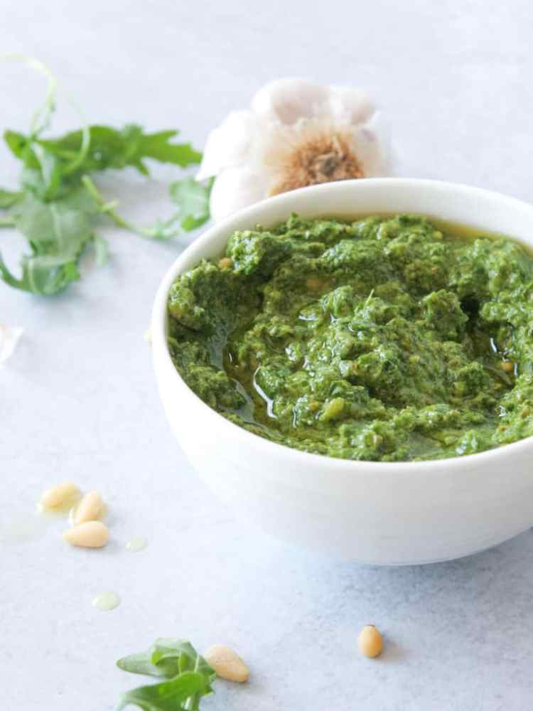 bowl of arugula pesto with garlic in the background and oil drizzle