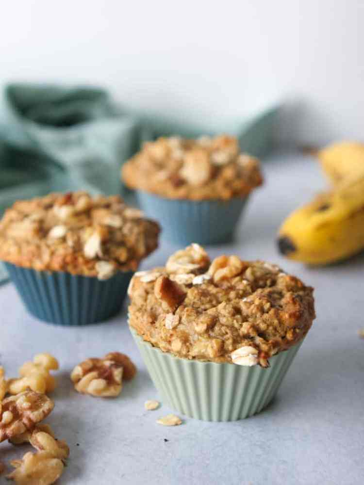 close up image of banana walnut oat muffins with a banana in the background and a sprinkle of rolled oats