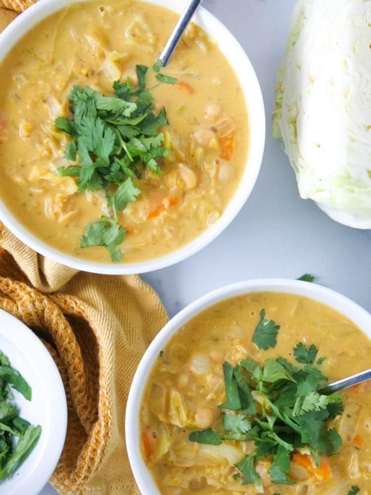 bowls of coconut cabbage soup with cilantro on top and a yellow towel.