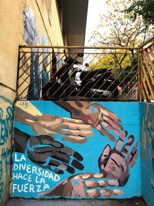 """mural of many hands painted on blue wall. white text reads, """"la diversidad hace la fuerza"""""""