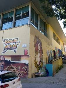 """facade of a building with graffiti on side that reads """"boca nord"""""""