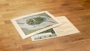 Two postcards on a wooden surface. The image on the postcard is two pairs of cupped hands around a plot of farmland.