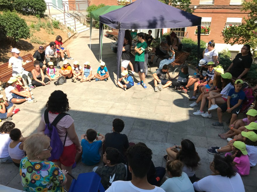 A group of about 50 children seated in a circle outside. A woman in painter's clothes is speaking to them.
