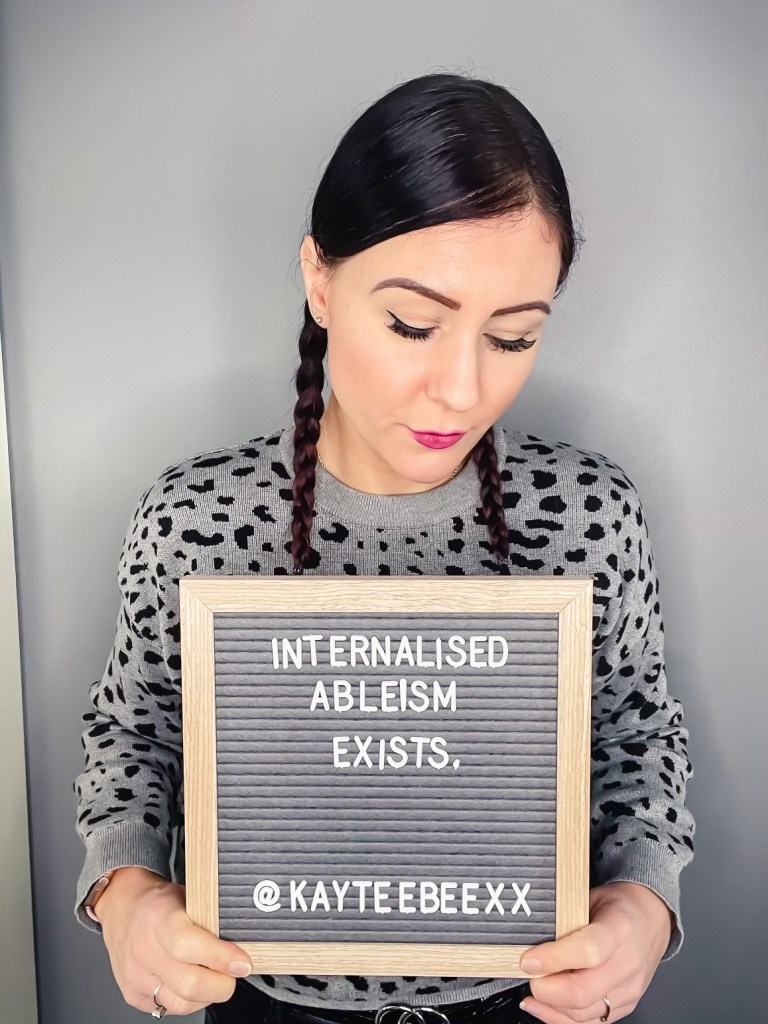 Me holding a board saying Internalised ableism exists.