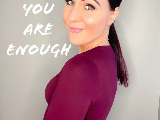 Me half facing the camera, my hair is in a pony tail and i am wearing a red top. There is a caption that says you are enough.