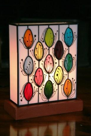 """Lampe contemporaine """"Pollen"""" en vitrail Tiffany constituée de verres plats américains opalescents de couleurs multiples. Dessins représentant des signes """"naïfs"""" peints à la grisaille et cuits à 650 °. Socle en béton ciré rouge basque lui assurant un aspect très moderne et une grande stabilité. Hauteur 28 cm, largeur 23 cm, épaisseur 11 cm"""