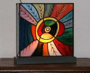 """Lampe """"Dzungla"""" en vitrail Tiffany, constituées de verres plats opalescents de multiple couleurs vives peints de feuillages naïfs à la grisaille et cuit à 620°. Socle en béton ciré gris anthracite lui assurant une grand stabilité. Poids 3,5 kg. Ampoule E14 de 40 W fournie. Eclairage lumineux. Largeur 27 cm profondeur 9 cm Hauteur 27 cm."""