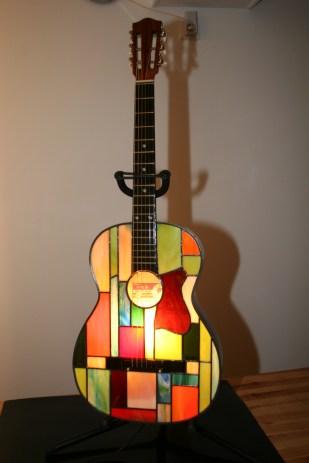 """Pièce d'exception : extrême originalité, design, élégance mais aussi """"fun"""" pour cette guitare électrifiée pouvant être posée au sol, sur un meuble ou suspendue au mur. Caisson de guitare véritable en bois dont le panneau avant a été remplacé par un panneau de vitrail constitué de verres opalescents vous garantissant un éclairage d'ambiance doux mais très lumineux. L'ampoule E14 fournie de 40 W peut être changée au moyen d'un système très simple (mode d'emploi fourni) permettant l'accés à l'ampoule. Pièce unique, signée et numérotée. Hauteur 95 cm, largeur 35 cm"""