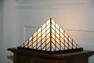 Lampe Pyramide en vitrail Tiffany. Verre opalescent blanc nacré. Socle en chêne massif teinté wengé. Eclairage doux mais lumineux. Dimensions socle 30*30 cm. Hauteur 30 cm