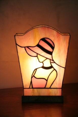 Lampe Camille en vitrail Tiffany. Verre opalescent de couleur rose et chair pour le personnage et rose à l'or strié de jaune doré pour le fond. Socle en noyer massif teinté wengé. Dimensions socle 14*9 cm. Hauteur 25 cm.