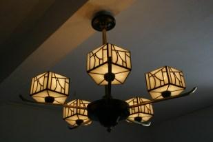"""Pièce d'exception, Pentalight II est le 2ème exercice de ce style : un élégant lustre ancien Art Déco des années 1930 entièrement rénové et électrifié. Les coupoles rondes initiales, jaunes, """"vieillotes"""" et sans caractère ont été remplacées pas 5 coupoles pentagonales d'aspect à la fois moderne et rétro, en vitrail Tiffany composées de 375 pièces de verre blanc nacré et opalescent assemblées à la soudure à l'étain patinée noire pour un aspect ancien. D'une taille imposante hors tout de 60 cm de hauteur et d'un diamètre de 80 cm, ce lustre apportera suffisamment de luminosité à votre intérieur, qu''il s'agisse d'une salle à manger, d'un salon ou d'une cuisine, sans """"l'agressivité"""" des luminaires traditionnellement choisis pour ces pièces, et diffusera une lumière chaleureuse, profonde et indirecte. Les 5 branches de Pentalight et la tige centrale sont en cuivre, d'origine. Les parties noires sont en chêne d'origine également mais ont été patinées en noir Napoléon (elles étaient de couleur marron foncé à l'origine). Sa patine ancienne et les traces laissées par le temps permettent à cette pièce de garder son aspect ancien."""