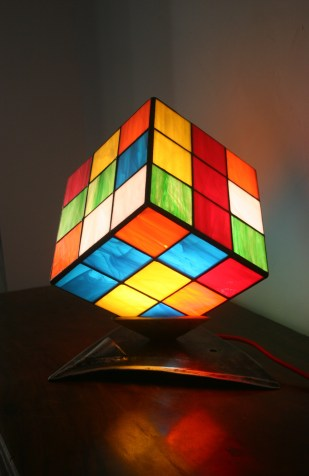 """Fusion d'une culture moderne et d'un outil ancestral : """"Nostal'Kub"""" est une lampe d'Art Contemporain particulièrement originale et unique. Elle évoquera le casse tête d'un objet culte des 80's, et la solidité intemporelle d'un soc de charrue du 19ème. Mariage de matériaux nobles, le Verre et l'Acier, pour une harmonie de construction moderne de style industriel. Très vive, gaie, colorée et lumineuse, cette lampe est constituée d'un cube de 6 pans de véritable Vitrail Tiffany, aux 6 couleurs traditionnelles à ce type de cube : rouge, vert, bleu, jaune, orange et blanc, posé sur l'un de ses angles dans un socle d'acier de 3 pans lui-même soudé sur un ancien soc de charrue (devenu socle !!!) le tout décapé et vernis mat."""