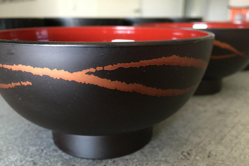 Reis- und Suppenschalen aus lackiertem Holz.