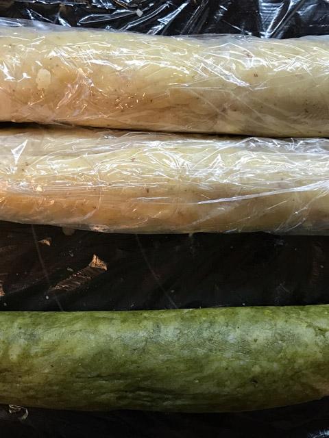 Der Teig für die Matcha- und Vanillekipferl wird zu Rollen geformt, in Folie eingewickelt und im Kühlschrank über Nacht gekühlt.