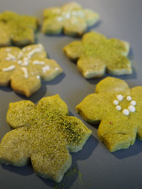 Fertig dekorierte feine Matcha-Keckse mit einer Glasur aus Puderzucker und Yuzusaft.