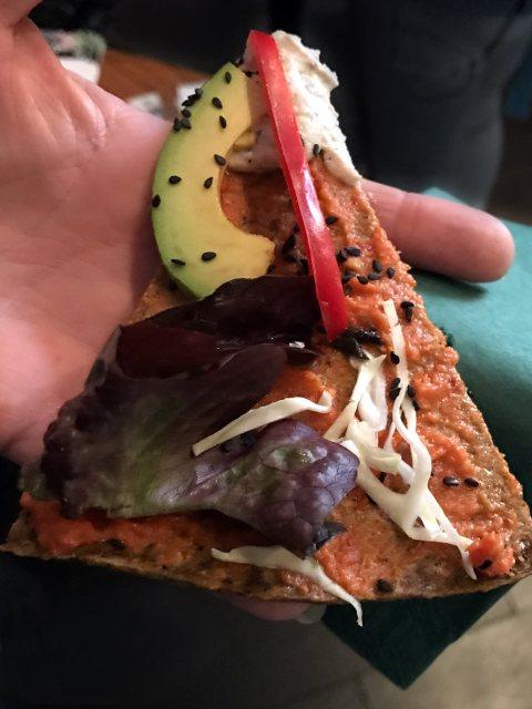 Die roh-vegane Version der Pizza mit einem Boden aus Buchweizen und Avocado, der 12 Stunden bei 42 Grad getrocknet wird. Als Belag: Avocado, Salat und Hanfsprossen.