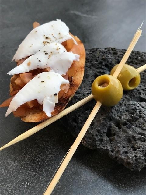 Frisch geröstetes Crustini mit Tomatenwürfeln und dünnen Scheiben Ziegenfrischkäse.