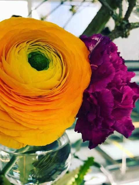 Blüten in kleinen Vasen an Zweigen.