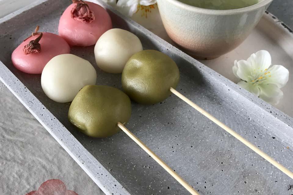 Hanami-Dango: dreifarbige Motchi-Spieße mit eingelegten Kirschblüten.
