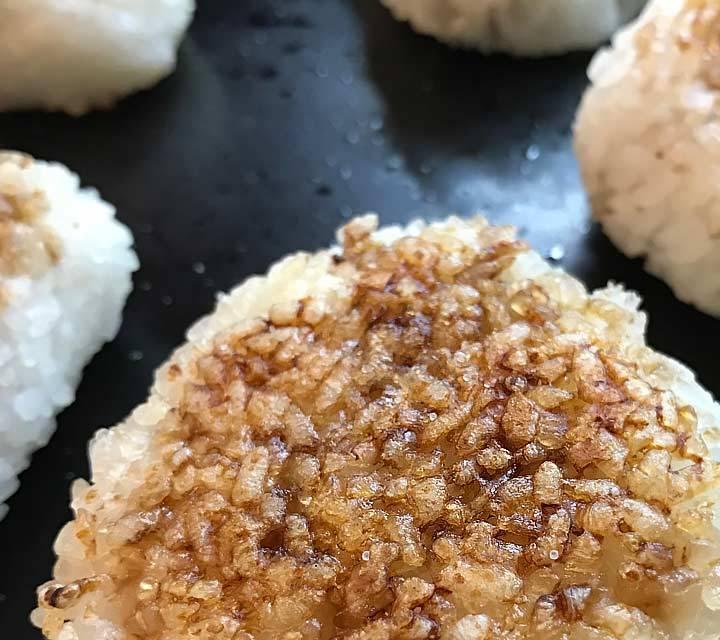 Yaki Onigiri: die knusprigen Reisbällchen müssen langsam und mit Gedult ohne Fett gebraten werden. Erst zum Schluss werden sie mit Sojasauce bestichen.
