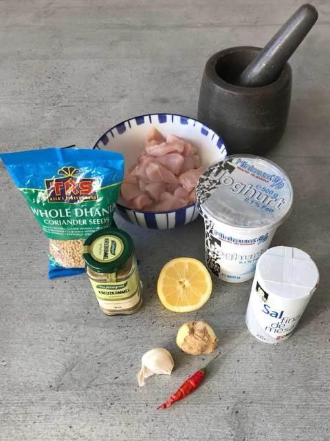 Die Zutaten für meine indische Tandoori-Pfanne mit Hühnchen: Natur-Joghurt, Hühnchenfilet, Zitrone, Ingwer, Knoblauch, Chili, Salz, Koriander, Kurkuma, Kreuzkümmel und Öl.
