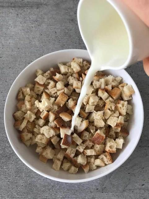 Das Weissbrot vom Vortag wird für die Semmelknödel klein geschnitten und in lauwarmer Milch eingeweicht.