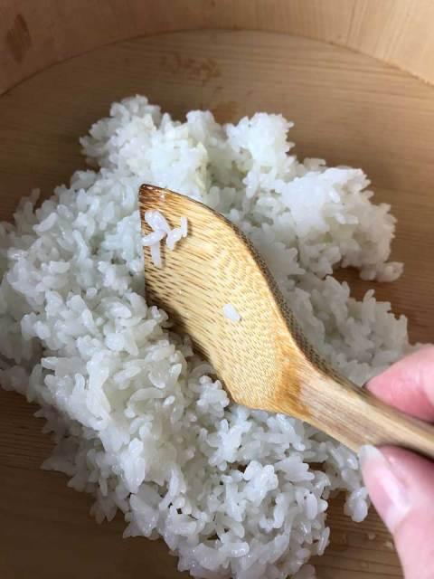 """Den gekochten Reis mit einem Holzlöffel vorsichtig """"durchschneiden"""" und wenden."""