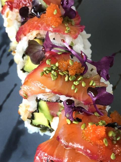 Amerikanische Sushirollen mit Lachs, Avocado, Gurke, Sesamkörnern, Fischrogen und Kressesprossen.