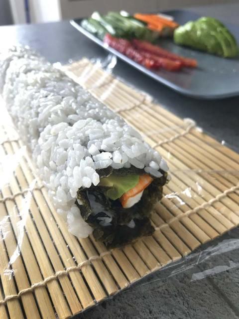Die California-Rolls mit der Sushi-Matte leicht andrücken und formen.